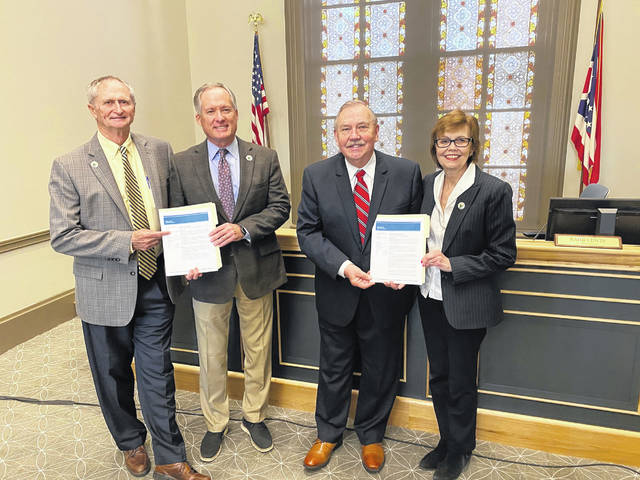 Pictured, left to right, holding copies of Moody's reports are Commissioner Gary Merrell, Commissioner Jeff Benton, Delaware County Auditor George Kaitsa and Commissioner Barb Lewis.