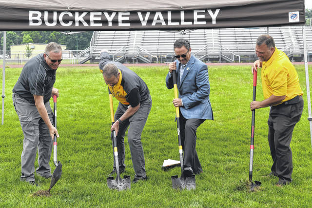 Buckeye Valley Board of Education President Justin Osborn, Superintendent Andy Miller, First Commonwealth Bank Senior Vice President Adam Hansberry and Director of Operations & Safety Jeremy Froehlich break ground Wednesday on a project to replace the current football field at Buckeye Valley High School with a turf field.