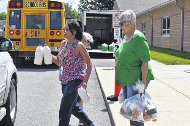 Volunteers Sarah Miller and Barb Rollins load milk and food into a car Tuesday morning as part of the Summer Lunch Program at Conger Elementary School.