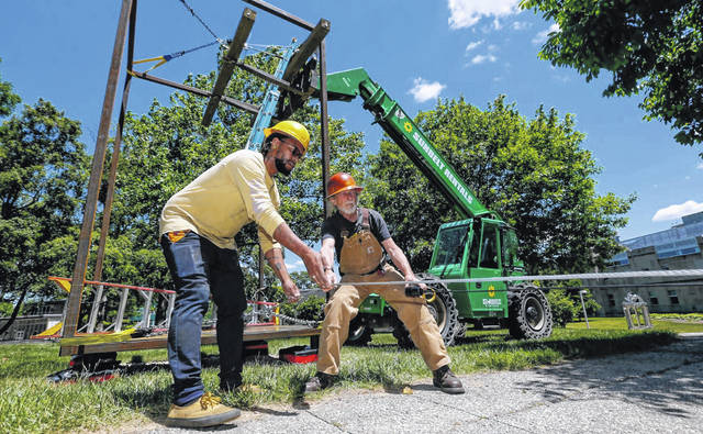 """Ohio Wesleyan graduate Andrew Wilson, left, works with sculpture professor Jonathan Quick to install Wilson's """"Back Porch"""" metal artwork on the academic side of campus. The 14-foot-tall metal sculpture honors OWU Black lives and legacies."""