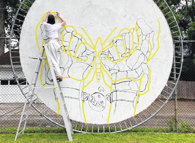 Ohio artist Brooke Ripley tapes off a butterfly on a repurposed trampoline at Boardman Arts Park in Delaware. The piece of artwork will be painted Sunday, June 27, as part of Project Freedom.