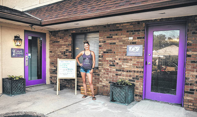 Local resident Tricia Grapner stands in between her two businesses — Canvas Creations for You (left) and Creations Venue (right) — located on South Sandusky Street in Delaware.