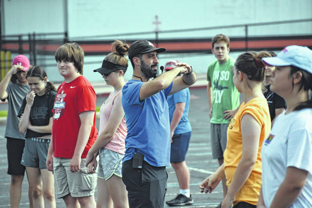 Band Director Andy Doherty walks between marching band members during practice Thursday and gives them instruction on proper posture during a show.