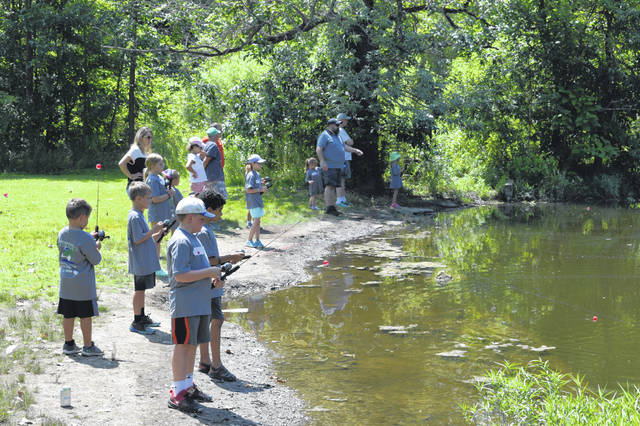 """Attendees of the 2019 """"Fish with a Cop"""" event cast their lines together at Blue Limestone Park in Delaware."""