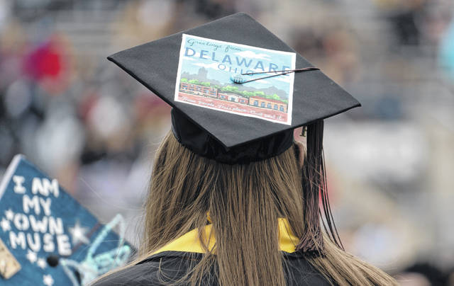 """An Ohio Wesleyan University graduate decorated her mortarboard with a postcard depicting the OWU campus. It reads, """"Greetings from Delaware Ohio. These people. This place. Can't beat it."""""""