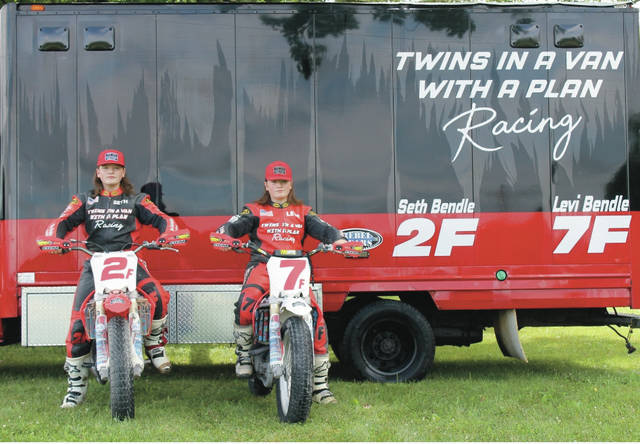 Seth and Levi Bendle pose in front of their trailer ahead of this weekend's American Motorcyclists Association (AMA) amateur grad national flat track races in Du Quoin, Illinois.