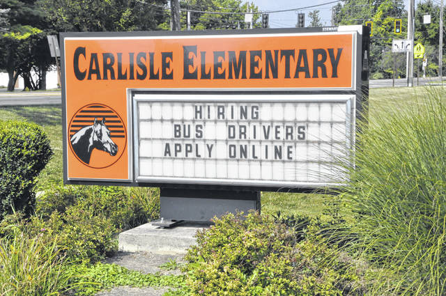 The monument sign outside Carlisle Elementary School in Delaware advertises the district's need for bus drivers. Delaware City Schools is also facing a substitute teacher shortage.