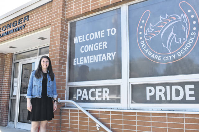 New Conger Elementary School Principal Mary Krell stands in front of the building she will be leading when classes begin on Aug. 18.