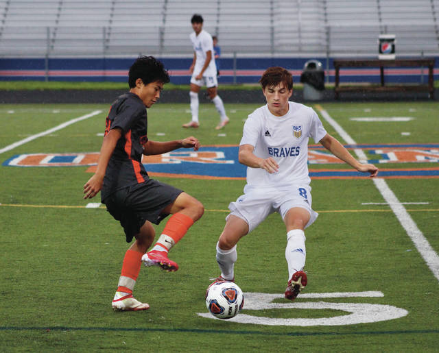 Olentangy Orange's Kai Kwak and Olentangy's Bennett Pinkerton (8) battle for possession during the first half of Tuesday's non-league showdown in Lewis Center.