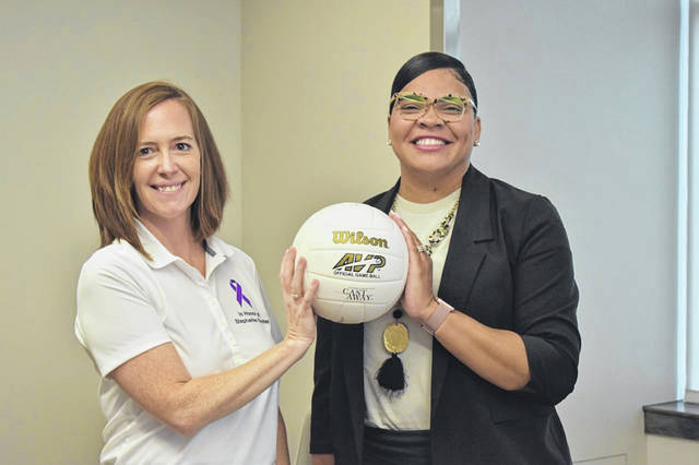 """Delaware County Prosecutor Melissa Schiffel, left, and Turning Point President and CEO Amber Scott hold a volleyball together Monday to promote the upcoming """"Volley Against Violence"""" event to be held Sept. 11 at the Food Truck Depot on Potter Street in Delaware."""
