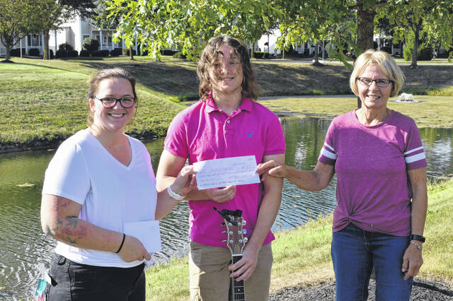 """Delaware residents Emily Bucksar, left, and Mary Bragg, right, present a check for $1,740 to Jacob Stewart, a local teen who saved a group of ducklings this year and earned himself the nickname """"Duck Dad."""""""