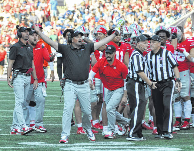 Ohio State head coach Ryan Day raises his arms in disbelief, while players and other coaches react to a replay on the video board after a Denzel Burke interception was overturned during the second quarter of the Sept. 18 home game against Tulsa.