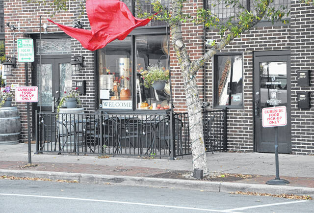 """Pictured are two """"curbside food pick-up only"""" signs located on East Winter Street in downtown Delaware."""