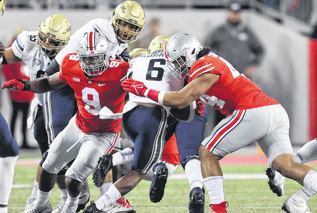 Ohio State's Zach Harrison (9) and J.T. Tuimoloau (right) combine to tackle Akron's Jonzell Norrils during Saturday night's game at Ohio Stadium in Columbus.