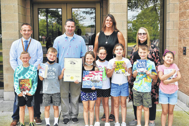 State Rep. Kris Jordan (R-Ostrander), center, is joined by Schultz Elementary School students (left to right) Max Woodruff, Alexander Emmons, Aurora Larson, Adalynn Singleton, Kaitlyn Brooks, Conner Bower and Bailey Chappell, as well as Principal Travis Woodworth (left), Superintendent Heidi Kegley (center) and LMC Assistant Rose Long (right).