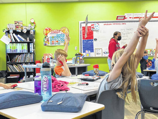 Students at Buckeye Valley West Elementary raise their hands during class last week.