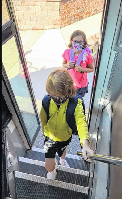 Claire Jutte, back, and Torian Kingsborough climb onto the bus during the safety video. Both students said they enjoyed taking part in the video.