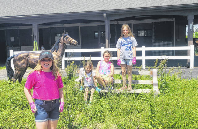 Prior to starting their Bronze Award project, which involved sprucing up some flower beds at the Delaware County Fairgrounds, several members of Girl Scout Troop 4837 posed for a photo inside the Jug Barn. Pictured, left to right, are Amelia Greasamar, Gwyneth Falk, Crimsen Myers and Olivia Falk.