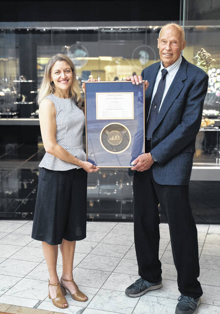 John C. Medici, of Ostrander, accepts the Carnegie Mineralogical Award from Gretchen Baker, director of the Carnegie Museum of Natural History.