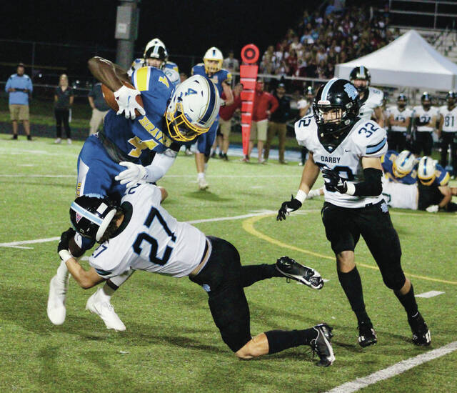 Olentangy's Dubby Agudosi (4) fights for extra yards as Hilliard Darby's Mac Link (27) tries to bring him down during the first half of Friday's OCC showdown in Lewis Center.