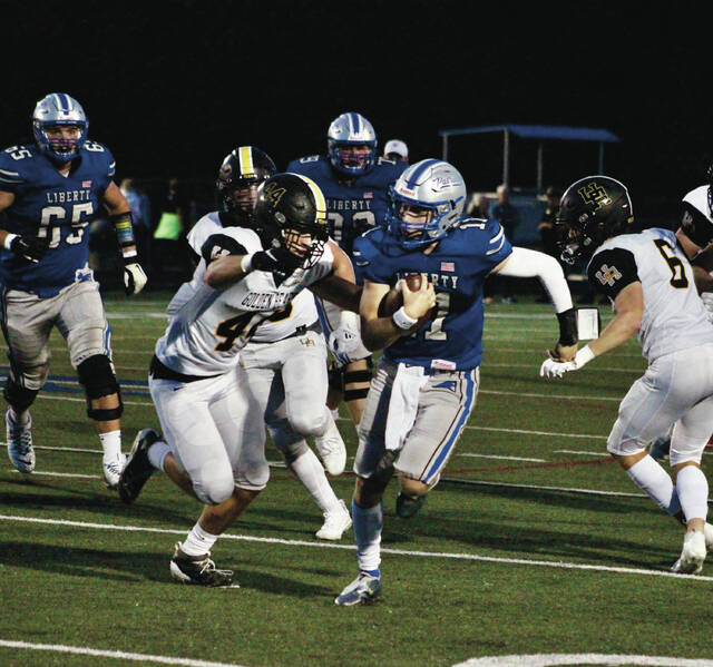Olentangy Liberty quarterback J.J. Sebert tries to elude Upper Arlington's Carter Brock (44) during the first half of Friday's league showdown in Powell.