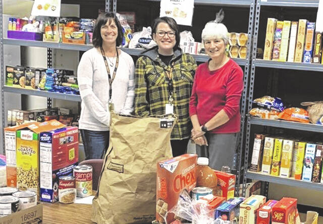 Staff at the Pacer Pantry stand among food and supplies donated by the community to the pantry, located at Willis Education Center. From left to right: Intern Jennifer Williams, Program Coordinator Carrie Hunt and Peg Watkins, who works at the district's Family Resource Center.