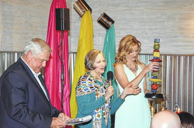 """2017 Bad Art, Good Folk participant Jean Bussell shares her artwork during last year's auction, with the help of auctioneer John Kramer and art """"model"""" for the evening, Heidi Bortel."""