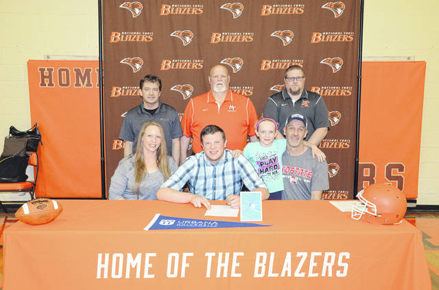 National Trail graduate Dalton Mason (front, second from left) is joined by family and coaches at his signing. Mason will play football at Urbana this fall.