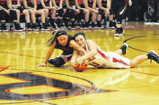 Preble Shawnee's Brenna Woodard battles with Madelyn Fearon of Arcanum for a loose ball. The Arrows came up short on the scoreboard, falling 66-51.