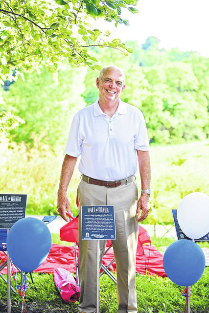 """Retired Judge Wilfrid Dues poses at the 2018 celebration with the plaque on the Hall of Honor path honoring Mary Gould Brooke 1858-1946 and Edith Gould, 1855-1946. Granddaughters of Cornelius Van Ausdal, these sisters left their own legacy in the form of the """"Brooke-Gould Memorial Fund"""" and its many substantial contributions to Eaton. Brooke provided leadership to the Preble County District Library, and was instrumental in establishing the first Preble County Historical Society, the Current Events Club and the Fort St. Clair Park. Gould's life focused on music, teaching piano lessons, and serving a close co-worker and compatriot with Brooke."""