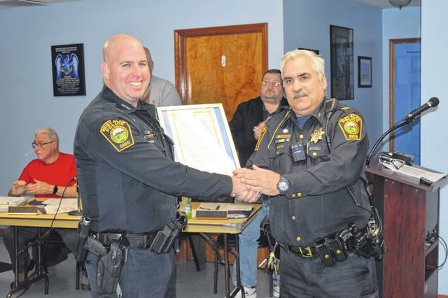 Officer Joshua Kaczmarek (left) was presented with a letter of commendation by West Alexandria Police Chief Tony Gasper (right) during the council meeting on Monday, April 1. Kaczmarek was honored for his work in stopping a dangerous criminal in connection with a homicide case in Lansing, Michigan.