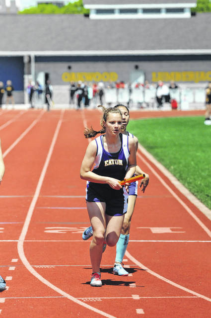 Eaton's Maddie Haynes takes the baton from teammate Jenna Aukerman during the 4x400 relay at the Southwestern Buckeye League track and field meet on Saturday, May 11.