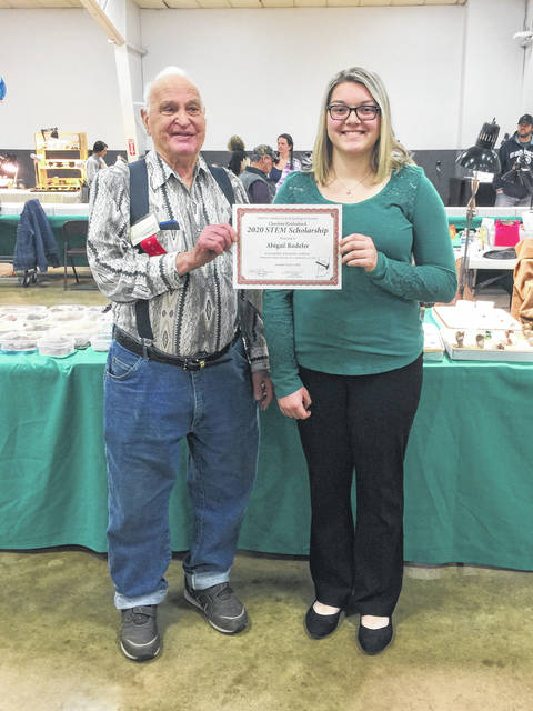 On behalf of the Eastern Indiana Gem & Geological Society, club member John LaMont presents the 2020 Charlene Reidenbach STEM Scholarship to Abigail Rodefer, a senior at National Trail High School.