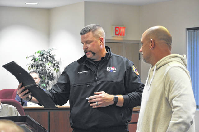 Eaton Fire/EMS Chief Brian Smith presents Tim Crase with the Fire Safety Commendation Award during the Eaton City Council meeting on Monday, Oct. 19.