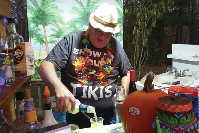 A projector screen provides a Hawaiian-style backdrop to the small kiosk where Fred Eck prepares drinks.