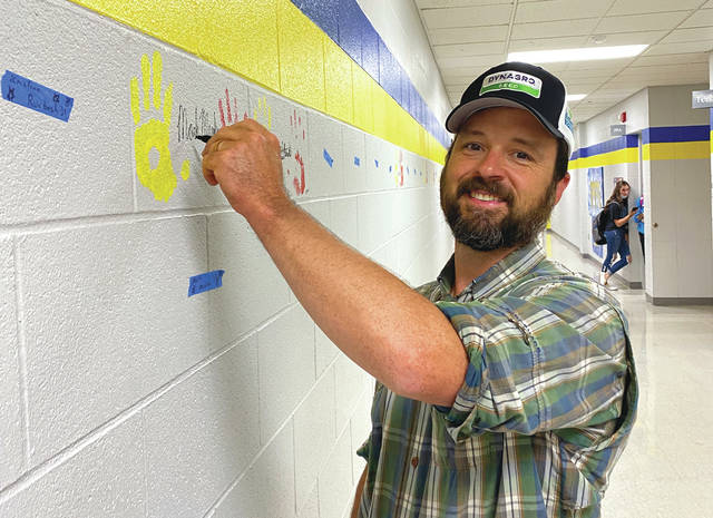 Former FFA member Mark Menke, who earned his State degree in 1998 and his American degree in 2000, places his handprint on the Ag Hallway wall at Twin Valley South.