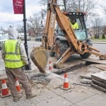 City workers pull up sidewalk
