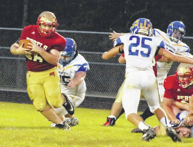 South Gallia junior A.J. Woodall, left, avoids a pair of Manchester defenders during a first half carry Friday night in a Week 4 non-conference football game in Mercerville, Ohio.