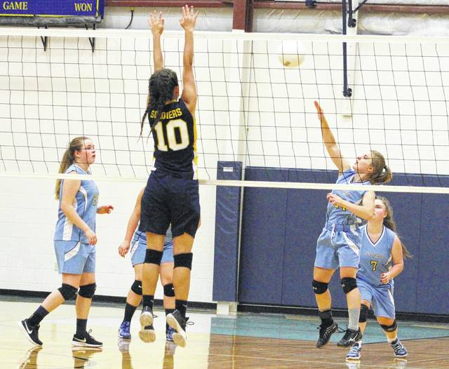 Ohio Valley Christian junior Makala Sizemore, right, hits a spike attempt during Game 3 of Tuesday night's volleyball match against Grace Christian in Gallipolis, Ohio.
