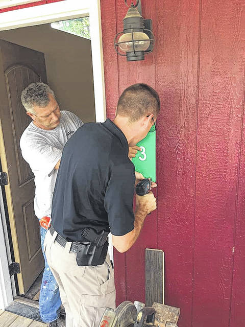 Rio Grande Police Lt. Josh Davies helps drill signs into a residence.