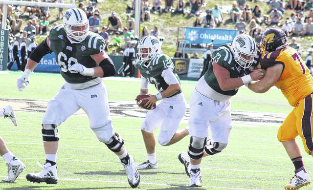 Ohio Sophomore Nathan Rourke (12) runs behind the block of Austen Pleasants (60) and Steven Hayes (73), during Rourke's first scoring run on Oct. 7 in Athens, Ohio.