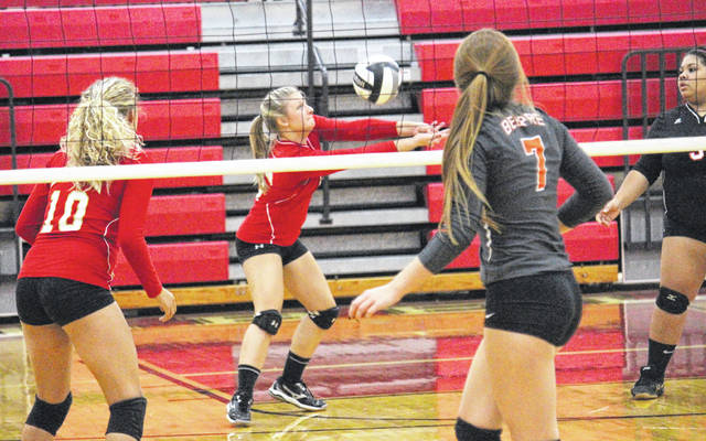 South Gallia's Hannah Shafer returns a serve as teammates Aaliyah Howell (10) and Keirsten Howell look on during the Lady Rebels' Tri-Valley Conference Hocking Division volleyball match against Belpre on Wednesday night in Mercerville, Ohio.