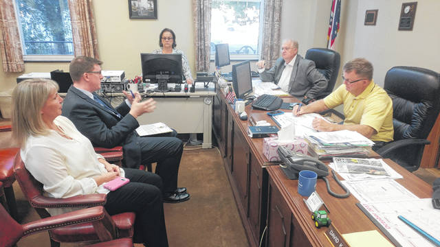 Gallia Prosecutor Jason Holdren, upper left, discusses the addition of a new victim's advocate during a meeting with the Gallia Commissioners Thursday. Director of Victim Services Regina Brown sits at his right. Commissioner Harold Montgomery, upper right, sits next to Commissioner Brent Saunders, lower right. Commissioner David Smith not pictured.