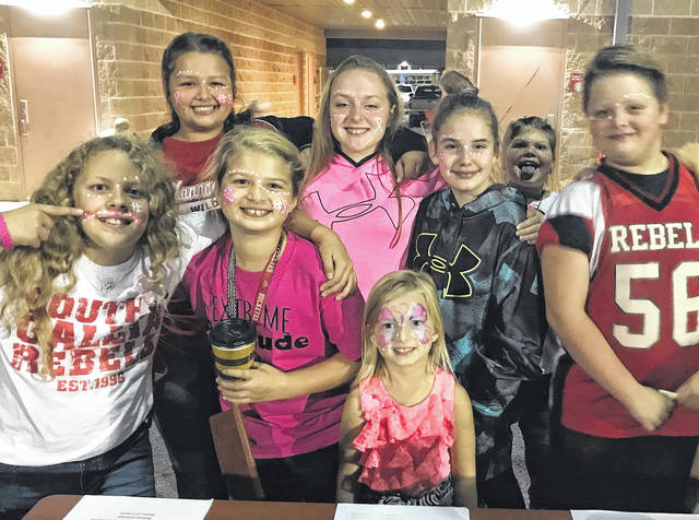 Students at the Pink Out football game pose for a picture after getting their faces painted in support of breast cancer awareness.