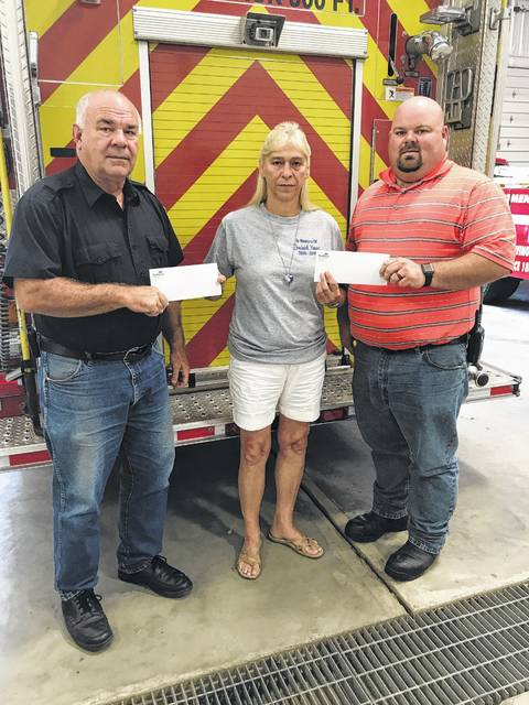 Barbara Hill presents Mike Null (left) of the Gallipolis Fire Department and Jeremy Bryant (right) of the Point Pleasant Fire Department, with donations for Fire Prevention Week. Both departments are visiting schools this week to educate children on fire safety.