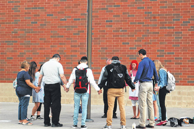 Students and some faculty at River Valley High School met outside before class started Wednesday to pray for their school and community.