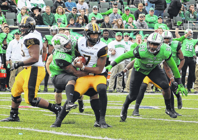 Marshall linebacker Frankie Hernandez (35) brings down Southern Miss quarterback Kwadra Griggs for a loss during the first quarter of Saturday's Conference USA finale at Joan C. Edwards Stadium in Huntington, W.Va.