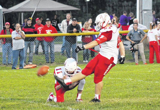 Wahama senior Christopher Hesson (right) kicks in one of three extra-points with sophomore Brayden Davenport (11) as holder, during the White Falcons' loss on Sept. 8 in Racine.
