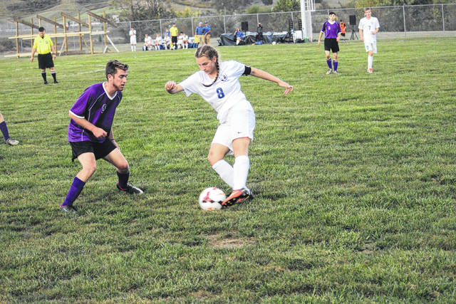 Gallia Academy's Gretchen McConnell (8) maintains possession of the ball during the Blue Devils' Ohio Valley Conference soccer match against Chesapeake on Sept. 28 in Centenary, Ohio. GAHS teammate Justin Day (7) looks on.