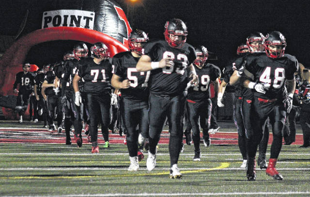 Point Pleasant seniors Jesse Gleason (63) and Cameron Nott (48) lead the Big Blacks onto the field for their regular season finale on Oct. 27 in Point Pleasant, W.Va.